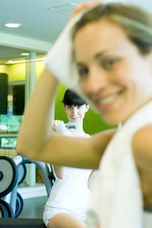 levantar peso: Two women in weight room, woman in foreground with towel around neck