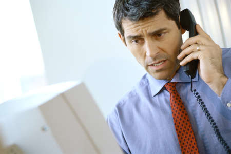 Businessman using phone, frowning and looking at computer LANG_EVOIMAGES
