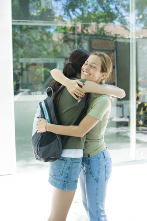 Two young women hugging each other, side view LANG_EVOIMAGES