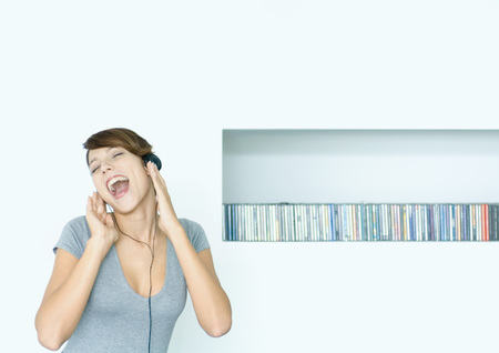 Young woman listening to headphones and singing, next to row of CDs, eyes closed LANG_EVOIMAGES