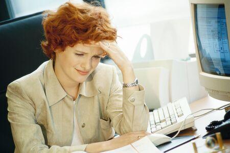 Businesswoman sitting at desk, holding head