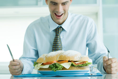 Man sitting holding knife and fork, looking down at large sandwich
