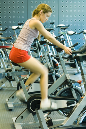 oneself: Woman sitting on stationary exercise bike