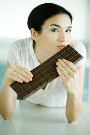 Woman holding large bar of chocolate and puckering lips