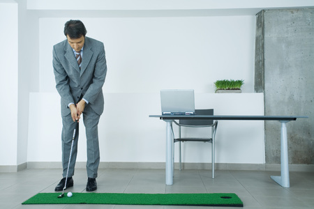 distractions: Businessman putting on artificial turf in office LANG_EVOIMAGES