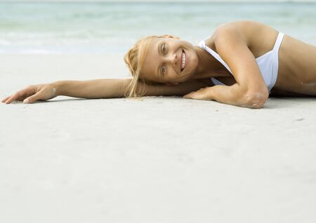 Woman lying on beach, smiling at camera