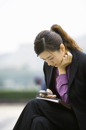 Businesswoman using messaging phone, leaning forward LANG_EVOIMAGES