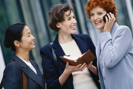 Three businesswoman, one holding agenda, one using cell phone