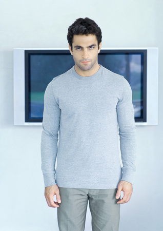 Man standing in front of wide screen TV, looking at camera LANG_EVOIMAGES