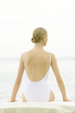 Adolescente sentado, vistiendo traje de baño, vista posterior LANG_EVOIMAGES