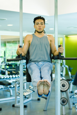 Man doing leg lifts with exercise machine