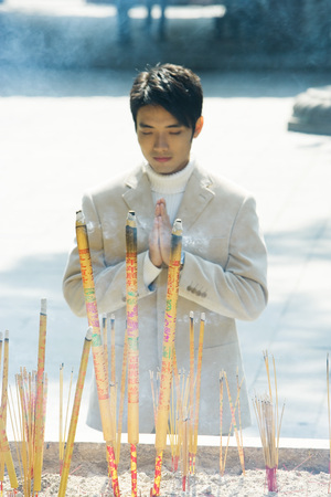 Young man praying in front of burning incense