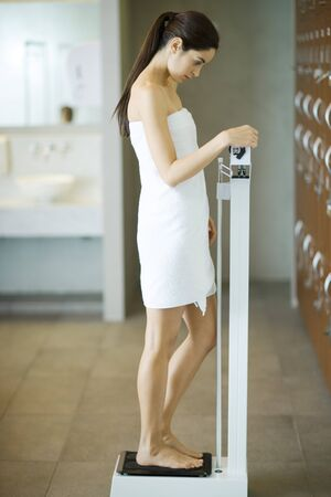 curiousness: Woman wrapped in towel, standing on scale, looking down