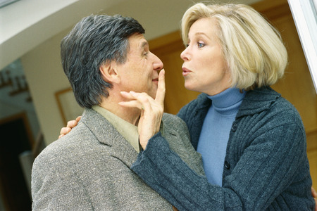 puckered lips: Senior couple, woman holding finger over mans mouth