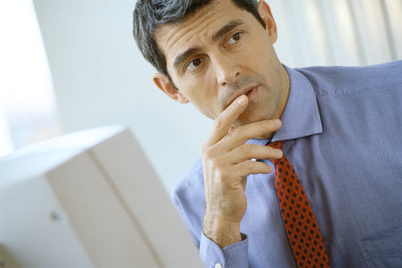 puzzlement: Businessman sitting at computer, finger at lip, looking away