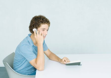 Teenage boy using cell phone LANG_EVOIMAGES