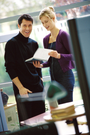 Two business colleagues looking at agenda, laughing