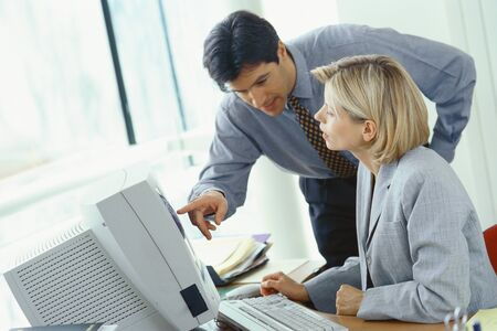 Businessman leaning over female colleagues shoulder pointing at monitor LANG_EVOIMAGES