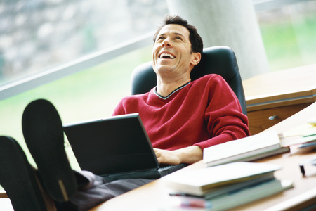 buena postura: Man sitting at desk with feet up, holding laptop on lap, laughing