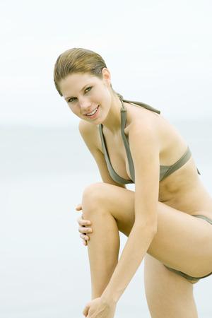 Mujer joven en bikini de pie con una rodilla arriba, tocando la pierna, sonriendo a la cámara LANG_EVOIMAGES