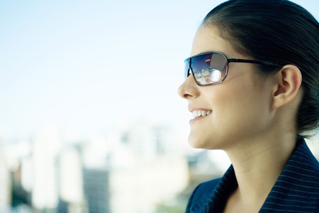 Woman wearing sunglasses, skyline in background, profile