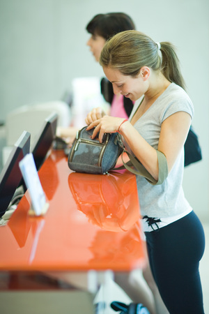 Young woman checking in at health club counter LANG_EVOIMAGES