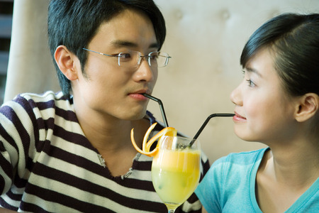 Young couple sharing cocktail with two straws