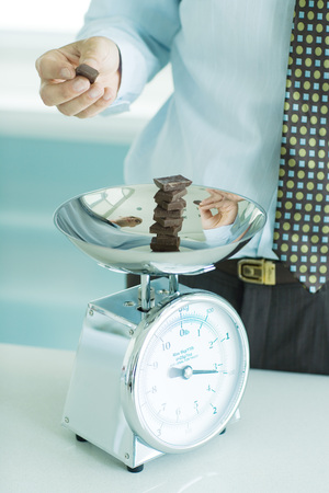 gaining: Man stacking chunks of chocolate on kitchen scale