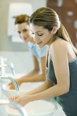 salud publica: Dos mujeres se lavan las manos en los baños públicos