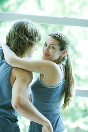 Young couple in exercise clothing standing by window, woman looking over shoulder, smiling at camera LANG_EVOIMAGES