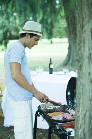meaty: Man grilling meat on barbecue