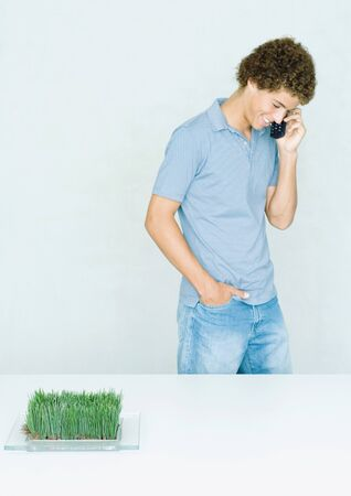 Teenage boy standing, using cell phone