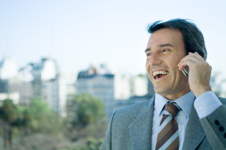 Businessman using cell phone and laughing, skyline in background