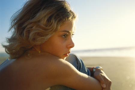 Girl sitting on beach, looking toward ocean, close-up