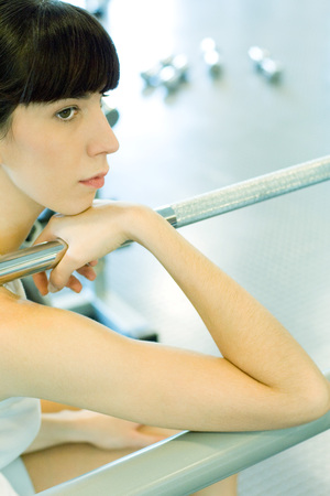 levantar peso: Woman sitting in weight room, holding on to metal bar, looking away