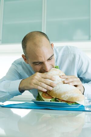 Man biting into large sandwich LANG_EVOIMAGES
