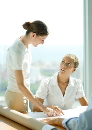 persuading: Two women discussing blueprints in office