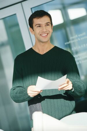 distractions: Young male office worker holding document LANG_EVOIMAGES