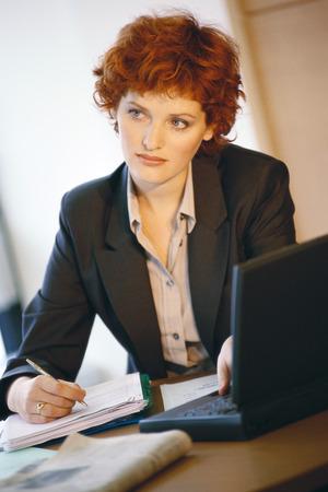 distractions: Businesswoman sitting at desk, portrait