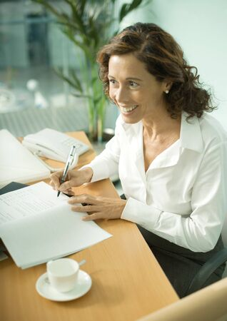 Mature professional woman sitting at table, smiling and looking out of frame
