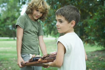 Two boys carrying tray of grilled meat LANG_EVOIMAGES