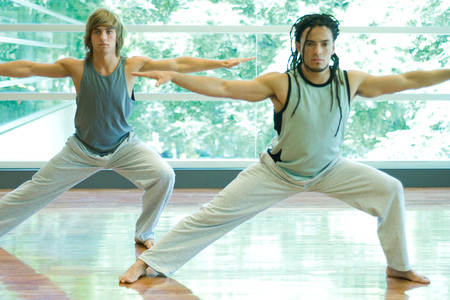 open windows: Young men doing side lunge in exercise class LANG_EVOIMAGES