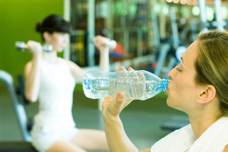 levantar peso: Dos mujeres en la sala de pesas, se centran en la mujer en primer plano beber una botella de agua