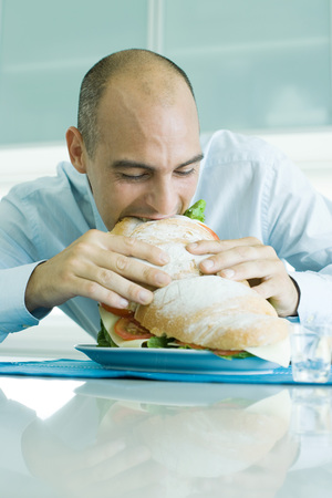 Man biting into large sandwich LANG_EVOIMAGES