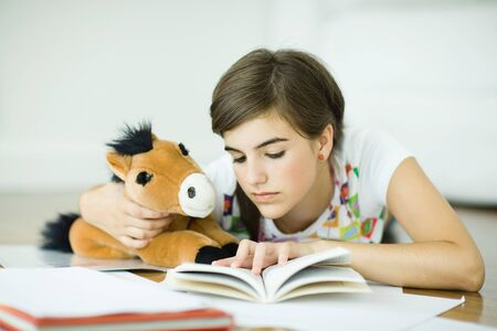 Teen girl lying on floor, holding stuffed toy horse and doing homework