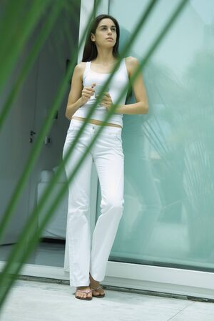 Woman standing by sliding glass door, holding cup, full length portrait LANG_EVOIMAGES