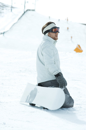 snowcovered: Young snowboarder kneeling on ski slope, looking away, side view