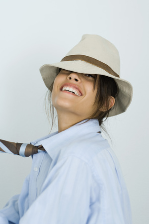 Teenage girl wearing tie and hat, head back, smiling at camera, portrait