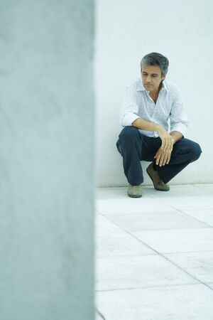 Mature man crouching, looking down, full length portrait