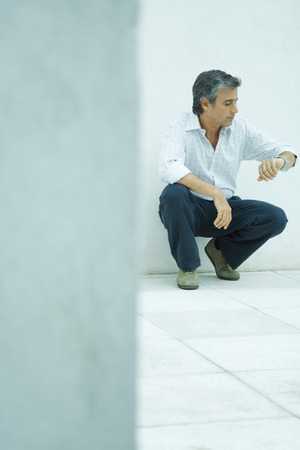Mature man crouching, checking watch, full length portrait LANG_EVOIMAGES